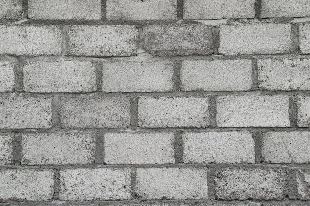 Grauer backstein rustikaler unvollendeter hintergrund