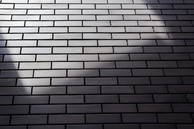 Grauer backsteinmauerhintergrund mit licht und schatten