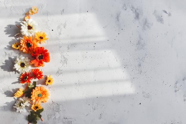 Grauer beton flach hintergrund mit bunten herbstblumenköpfen