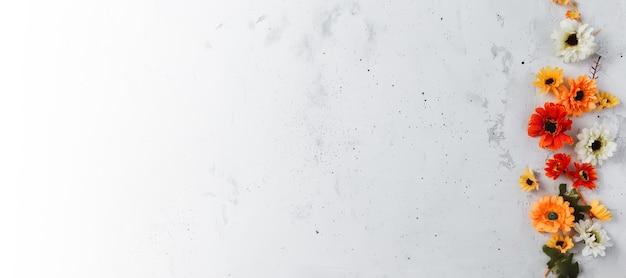 Grauer beton flach hintergrundfahne mit bunten herbstblumenköpfen