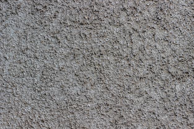 Grauer beton mit kleinen steinen