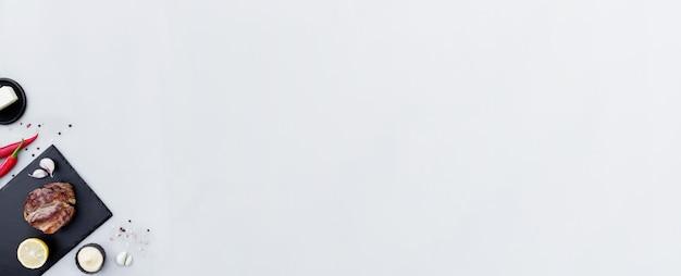 Grauer betonhintergrund flach mit schnitt von mittel-seltenem roten ribeye-fleischsteak auf schwarzem schneidebrett, zitrone, pfefferwürze, salz, mayonnaise-sauce, knoblauch, butter. rib-eye filet mit textfreiraum