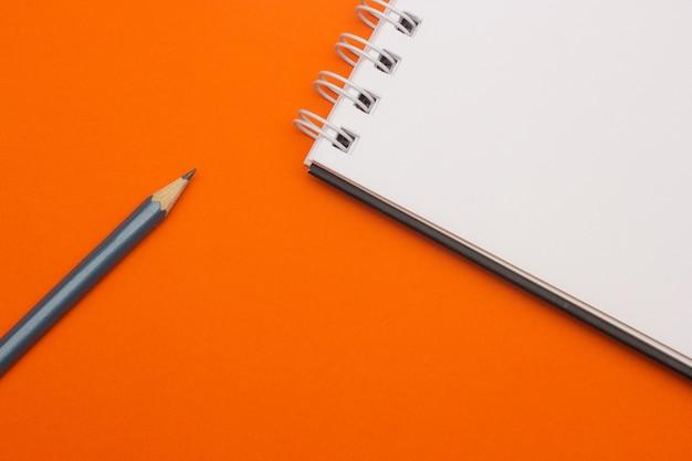 Grauer bleistift auf orange hintergrund, zurück zu schule, bildungskonzept