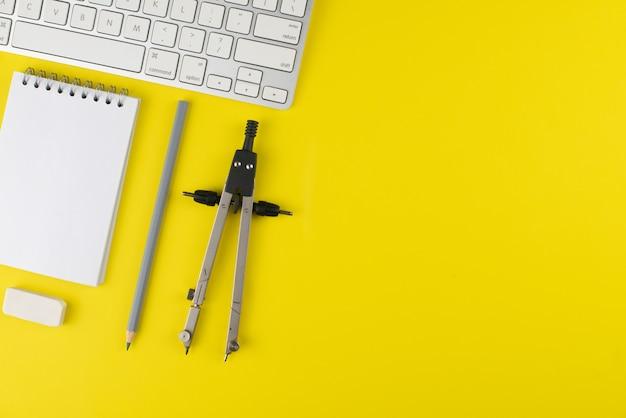 Grauer bleistift- und notizblockplaner, tastatur, gummi löschen, teiler auf gelbem hintergrund