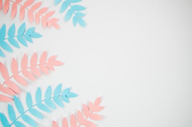 Grauer exemplarplatzhintergrund mit rosafarbenem und blauem laub