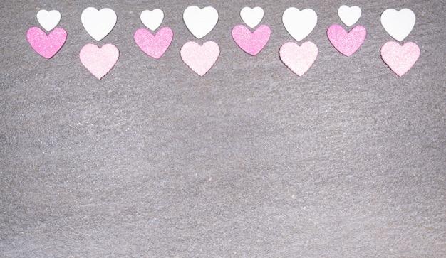 Grauer granithintergrund mit rosa und weißen herzen für valentinstag