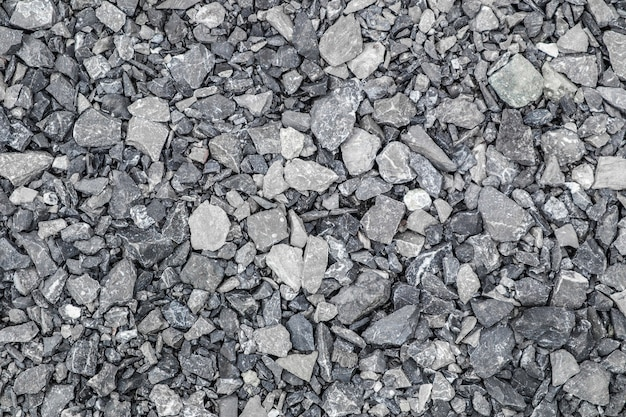 Grauer grundsteinschutthintergrund vieler kleiner steine.