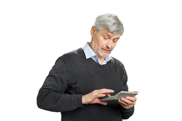 Grauer haarmann, der am taschenrechner arbeitet. reifer mann, der finanzen auf weißer nahaufnahme berechnet.
