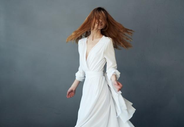 Grauer hintergrund der frau im weißen kleid attraktiver anblick glamourleistung. hochwertiges foto