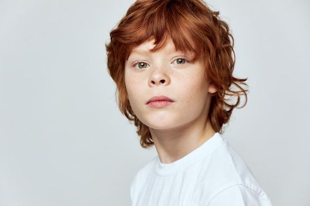 Grauer hintergrund des niedlichen rothaarigen kindes beschnittene ansicht des weißen t-shirtgesichts-nahaufnahme