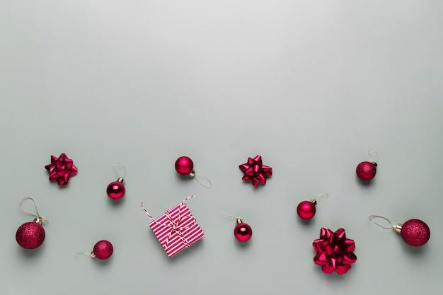 Grauer hintergrund mit rosa weihnachtsgeschenkbox vorhanden, kleine rote weihnachtskugeln oder kugelspielzeug, bandschleifen für tannenbaum, andere dekorationen. weihnachtsverkauf, shopping oder grußkarte oder einladung