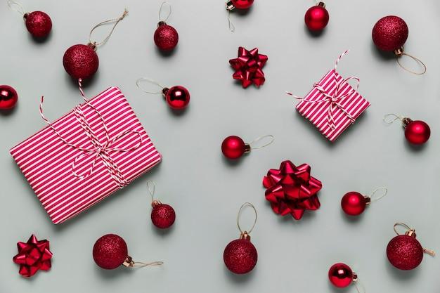 Grauer hintergrund mit zwei rosa weihnachtsgeschenkboxen, kleinen roten weihnachtskugeln oder kugelspielzeug, bandschleifen für tannenbaum. konzept für festliche verkäufe, werbeaktionen, grußkarten oder einladungsfotos