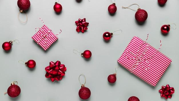 Grauer hintergrund mit zwei rosa weihnachtsgeschenkboxen rote ballspielzeugkugeln bögen