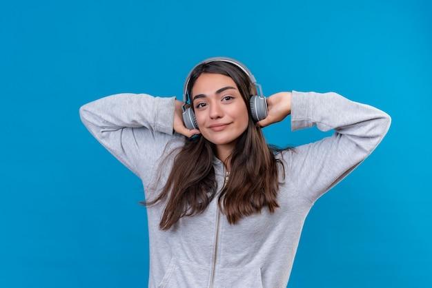 Grauer kapuzenpulli des jungen schönen mädchens, der kamera mit guter laune betrachtet und kopfhörer hält, der auf ohr steht über blauem hintergrund