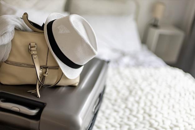 Grauer koffer mit handtasche und sommerhut, der bereit ist, den urlaub auf dem bett zu hause oder im hotel zu reisen
