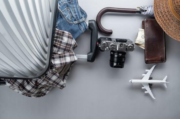 Grauer koffer verpackt für das reisen mit minimalem flugzeug, kleidung und zubehör - reisekonzept