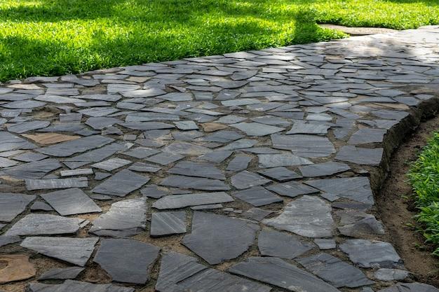 Grauer kopfsteinpflaster am parkgehweg. gartenweg aus grauem pflasterstein