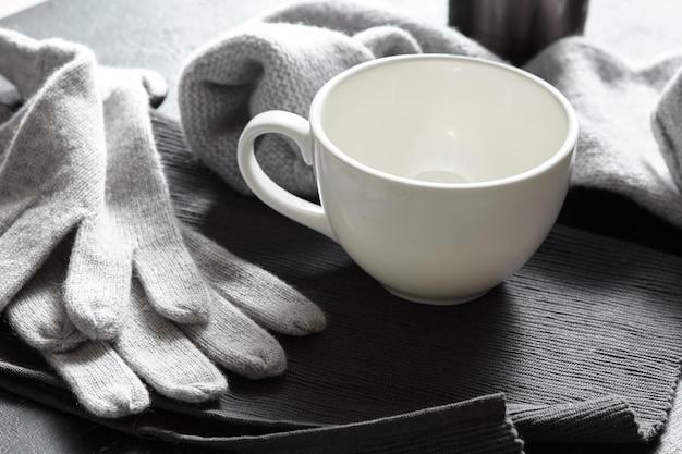 Grauer kuscheliger strickpullover mit einer tasse kaffee auf einem schwarzen holztisch