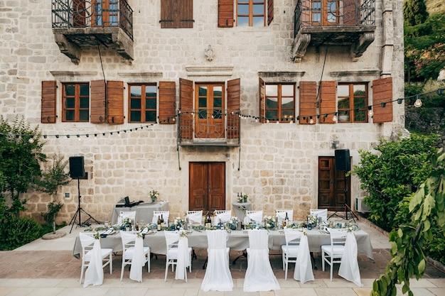 Grauer langer rechteckiger tisch des hochzeitsessentischempfangs und vierzehn stühle vor der alten villa