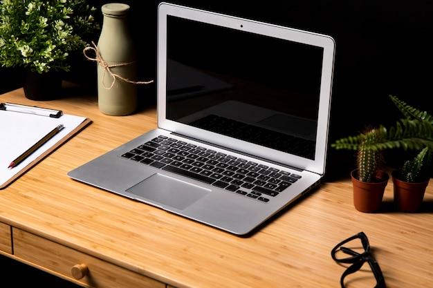 Grauer laptop auf einfachem hölzernem schreibtisch