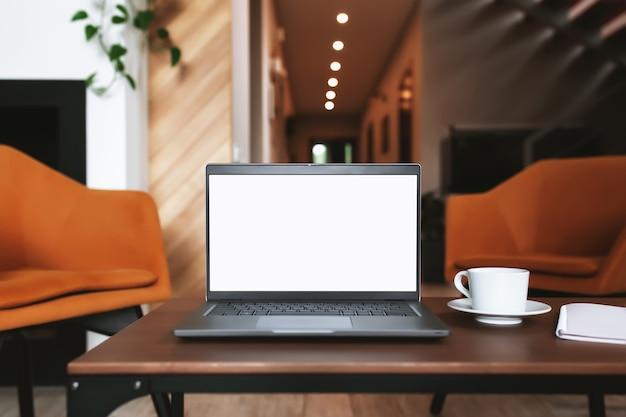 Grauer laptop-computer mit leerem weißen bildschirm auf holzcouchtisch, notizblock, stilvollem zimmer