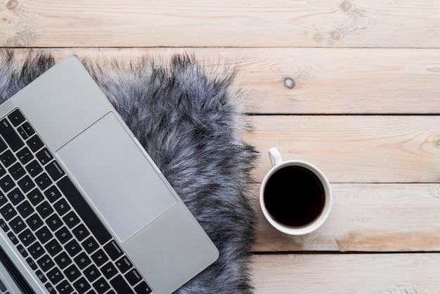 Grauer laptop mit kaffee auf hölzerner tabelle
