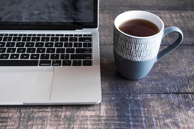 Grauer laptop mit kaffee auf holztisch