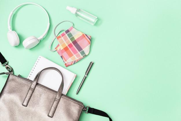 Grauer lederrucksack mit schulmaterial und persönlicher schutzausrüstung.