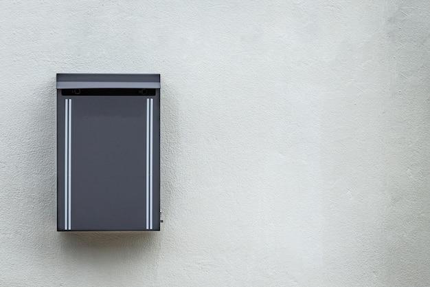 Grauer metallbriefkasten angebracht an der zementwand