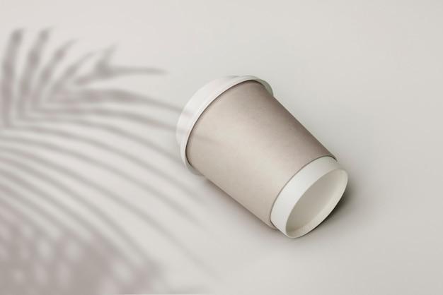 Grauer pappbecher mit palmblattschatten
