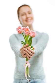 Grauer pullover der jungen schönen frau gibt rosa tulpen auf weißem hintergrund. unscharfes porträt, selektiver fokus. 8. märz und muttertag.