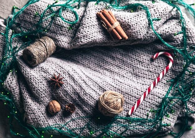 Grauer pullover und gerland mit weihnachtsschmuck.