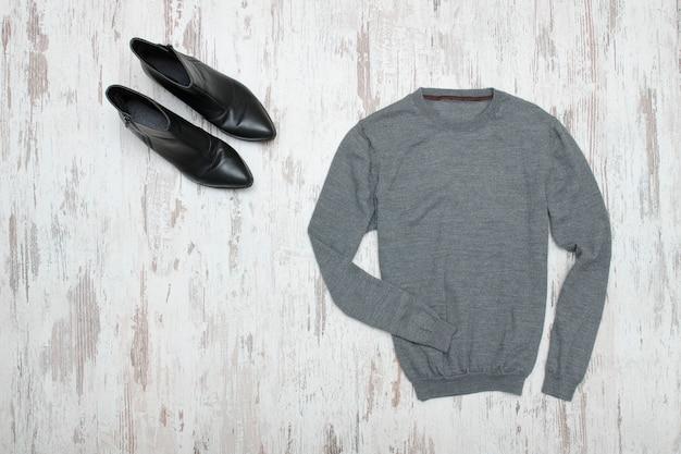 Grauer pullover und schwarze schuhe.