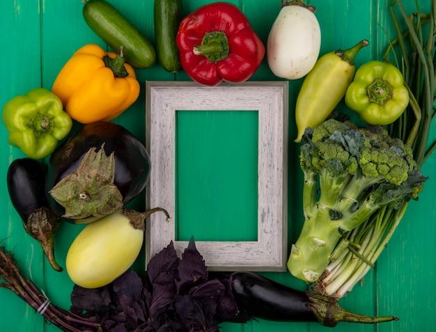 Grauer rahmen des kopierraums der draufsicht mit basilikum-paprika-auberginen-gurken-frühlingszwiebeln und brokkoli auf grünem hintergrund