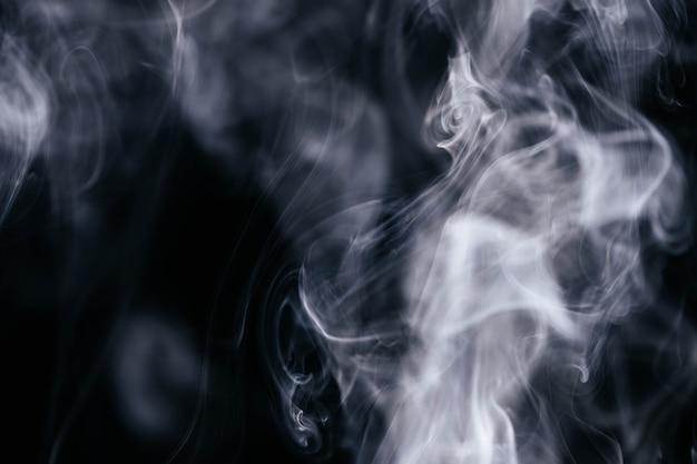Grauer rauch bewegt auf schwarzen hintergrund wellenartig