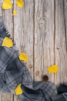 Grauer schal und trockene blätter von gelber farbe auf holzoberfläche