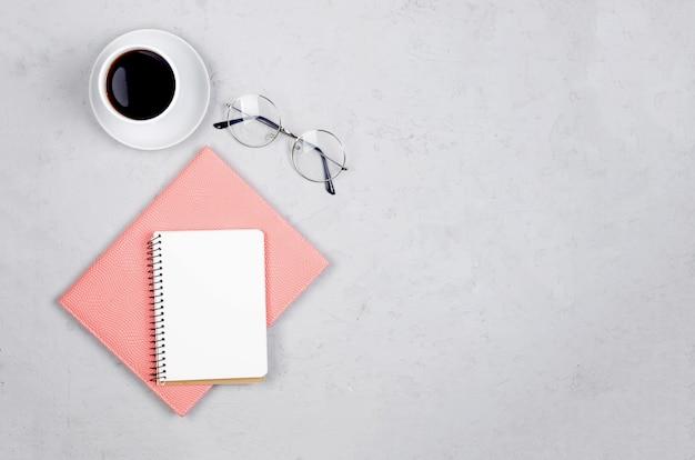Grauer schreibtisch am arbeitsplatz mit notizbüchern, leerem rohling, vorräten, gläsern und einer tasse kaffee.