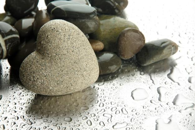 Grauer stein in form eines herzens, auf licht