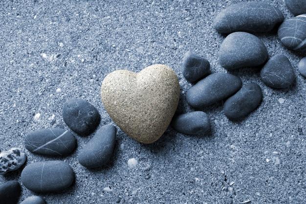 Grauer stein in herzform, auf sandfläche