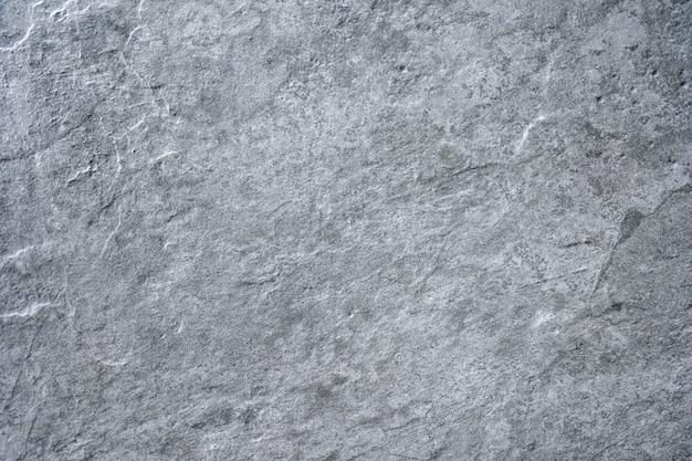 Grauer steinbeschaffenheitszementbeton, mit stein verputzter wandstuck, gemalter flacher verblassender hintergrund des marmorgrauen festen bodenkorns. grobe obere graphitkeramikfliese. dekoration für zu hause.