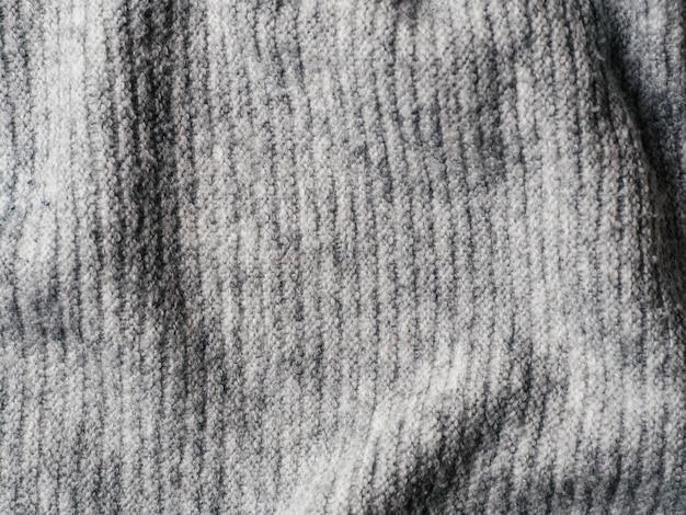 Grauer strickjackengewebebeschaffenheitshintergrund