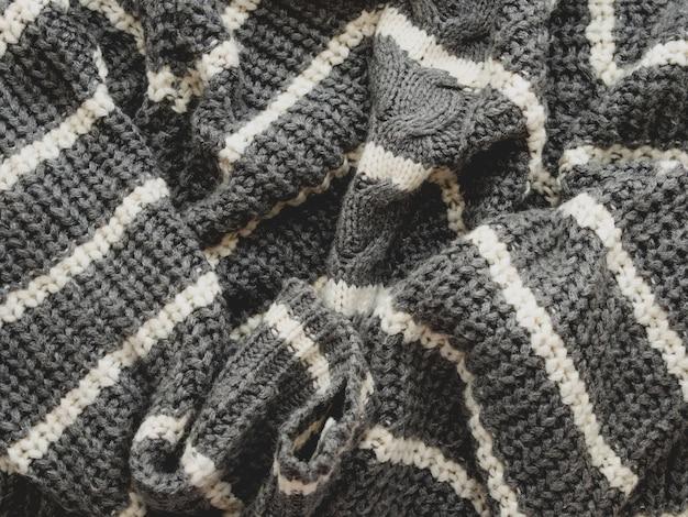 Grauer strickpullover mit weißen streifen. gefaltete warme kleidung. zerknitterter textilhintergrund.