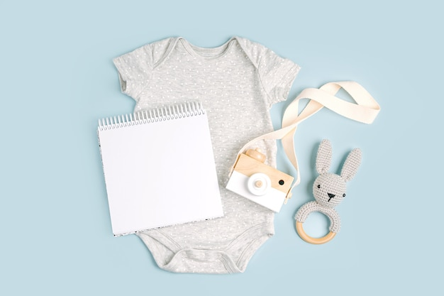 Grauer süßer babybody mit mock-up-karte. set kinderkleidung und accessoires. mode neugeborenes. flache lage, ansicht von oben