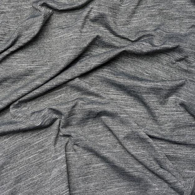 Grauer synthetischer bunter stoff zum nähen von kleidung, stoff zerknittert, nahaufnahme