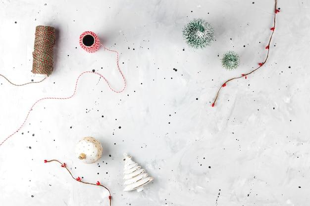 Grauer weihnachtshintergrund mit dekorkranz und weihnachtsbaumkugeln flach kopienraumhintergrund