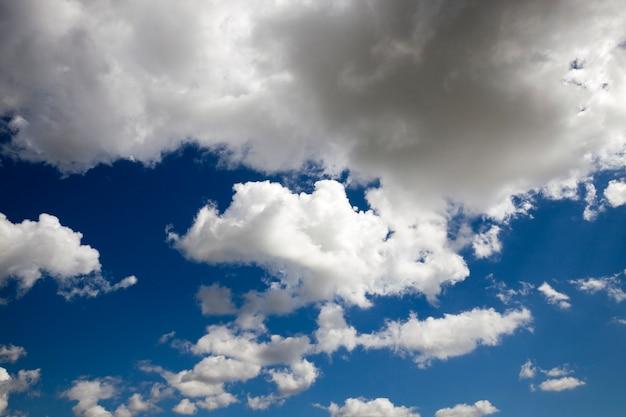 Grauer weißer himmel mit cumuluswolken von großer größe, blauer himmel beleuchtet durch sonnenlicht