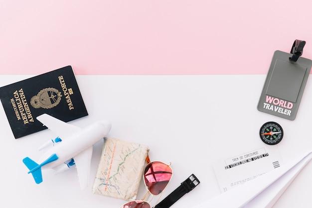 Grauer weltreisender-tag mit pass; karte; kompass; tickets; spielzeugflugzeug; sonnenbrille und armbanduhr auf doppeltem hintergrund