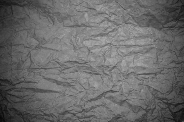Grauer zerknitterter hintergrund des strukturierten papiers.