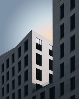 Graues betongebäude unter dem blauen himmel Kostenlose Fotos