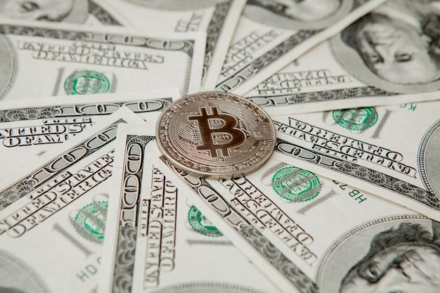 Graues bitcoin auf us-dollar-scheinen. konzept des elektronischen geldwechsels